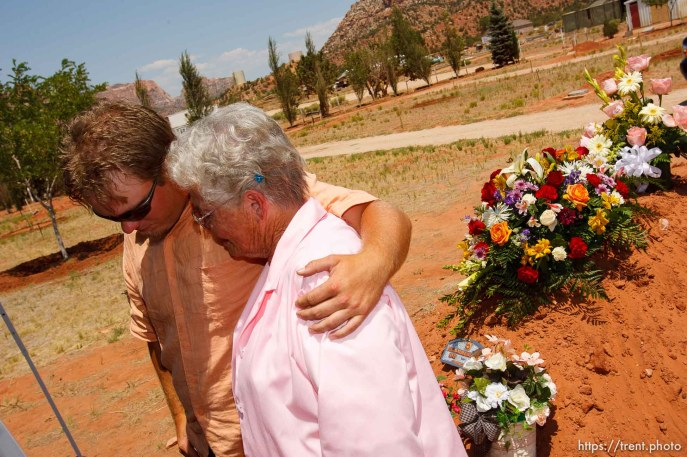 "Colorado City - Chad Lauritzen (left, a grandson) and Geri Harding (a sister) comfort each other as friends and family members of Norene Jeffs gathered in the Colorado City cemetery to remember this plural wife, who had been buried the previous week in a secret funeral by members of the Fundamentalist Church of Jesus Chris of Latter-Day Saints (FLDS). Jeffs, who had been ""sealed"" to the previous FLDS prophet Rulon Jeffs (Warren Jeffs' father), was buried even before family members exiled from the secretive church were notified of her death."