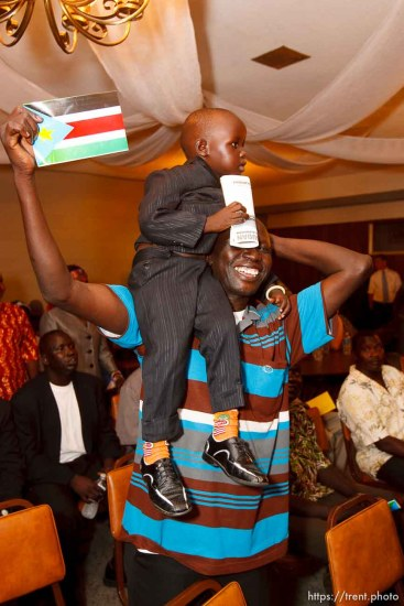 Trent Nelson | The Salt Lake Tribune Mamer Ngong holds up Alayou Aew during the national anthem at the South Sudan Independence celebration in Salt Lake City, Utah, Saturday, July 9, 2011