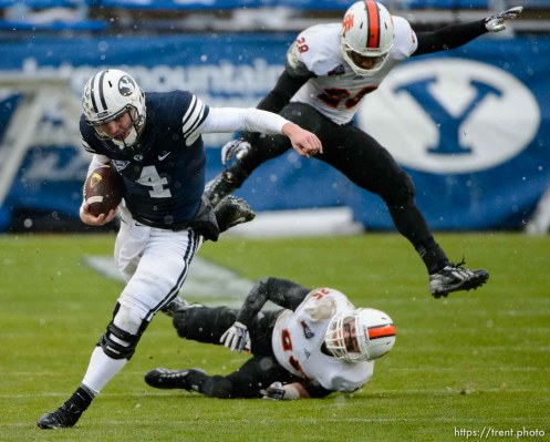 Trent Nelson | The Salt Lake Tribune Brigham Young Cougars quarterback Taysom Hill (4) runs the ball as BYU hosts Idaho State, college football at LaVell Edwards Stadium in Provo, Saturday November 16, 2013. Idaho State Bengals defensive back Tanner Davis (25) and defensive back Cameron Gupton (28) at rear.