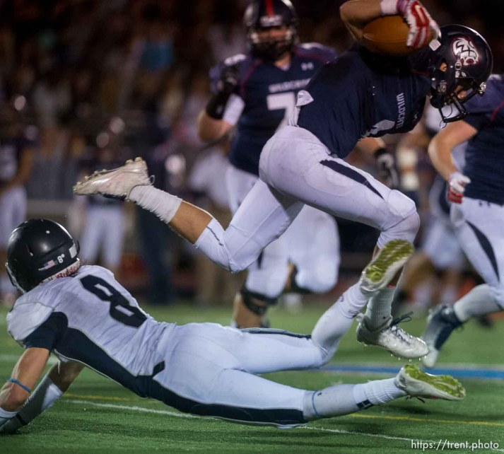 Trent Nelson | The Salt Lake Tribune Woods Cross's Braxton Gunther leaps over Corner Canyon's Jake Cahoon as Woods Cross hosts Corner Canyon High School football, in Woods Cross, Wednesday October 15, 2014.