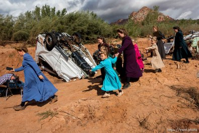 Trent Nelson | The Salt Lake Tribune A group of FLDS women quickly leave the scene of a flash flood incident as a TV cameraman begins filming, Wednesday September 16, 2015.