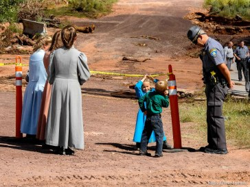 Trent Nelson | The Salt Lake Tribune Mohave County Sheriff's Deputy Matt Giralde answers questions from some young FLDS onlookers along the Short Creek Wash in Colorado City, Arizona, Wednesday September 16, 2015. The Utah National Guard and law enforcement on Wednesday resumed searching for the last known victim of a flash flood that tore through this polygamous border town home to followers of Warren Jeffs, leaving 13 dead and three injured, all of them women and children.