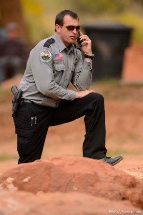 Trent Nelson | The Salt Lake Tribune A Colorado City/Hildale Marshal on the phone at a memorial for the 13 (and 1 still missing) victims of a September 14th flash flood. The memorial was held in Maxwell Park in Hildale, Saturday September 26, 2015.