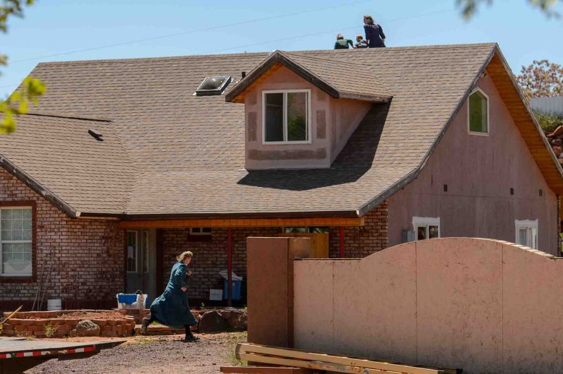Trent Nelson | The Salt Lake Tribune An FLDS woman runs away and another scurries her children off the roof as Mohave County Constable Mike Hoggard arrives to post a second eviction notice on a Colorado City, AZ, home, Monday May 1, 2017.