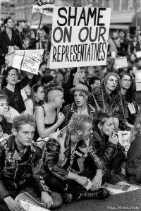 "Punks with ""shame on our representatives"" sign at an anti-war protest the night the air campaign of the Gulf War began. Market Street, San Francisco, California, January 16, 1991."