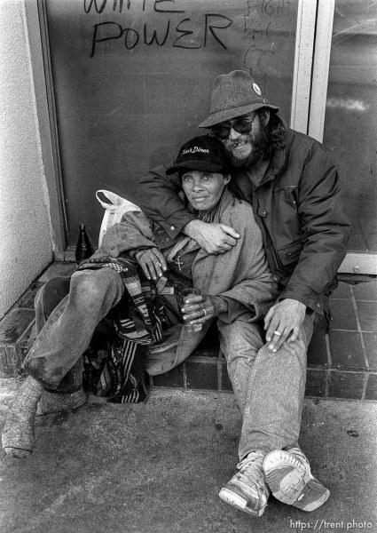 """Homeless couple under """"white power"""" graffiti."""