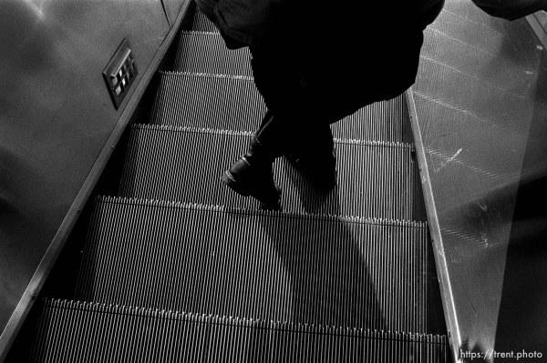 Person's feet on escalator
