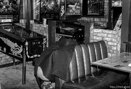 Alex Van Valin hiding behind booth near pinball machines at the Pie Pizzeria