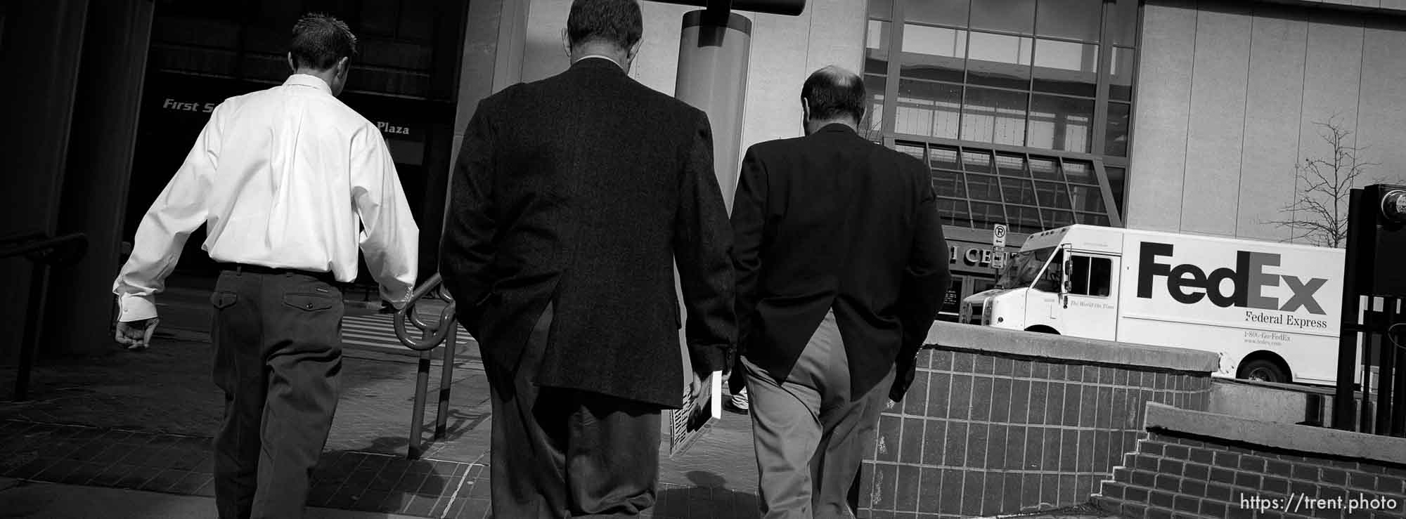 Three businessmen walking at lunch time.