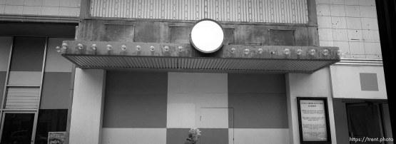 Woman walks by old Utah Theater marquee.