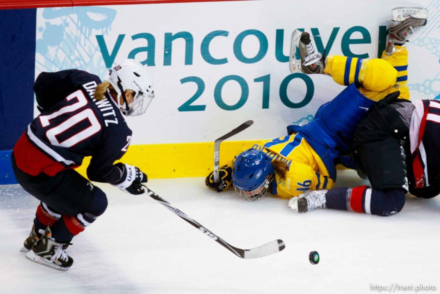 Sweden's Pernilla Winberg flips over USA's Meghan Duggan. USA's Natalie Darwitz at left. USA vs. Sweden, women's hockey, at the XXI Olympic Winter Games in Vancouver, Monday, February 22, 2010.