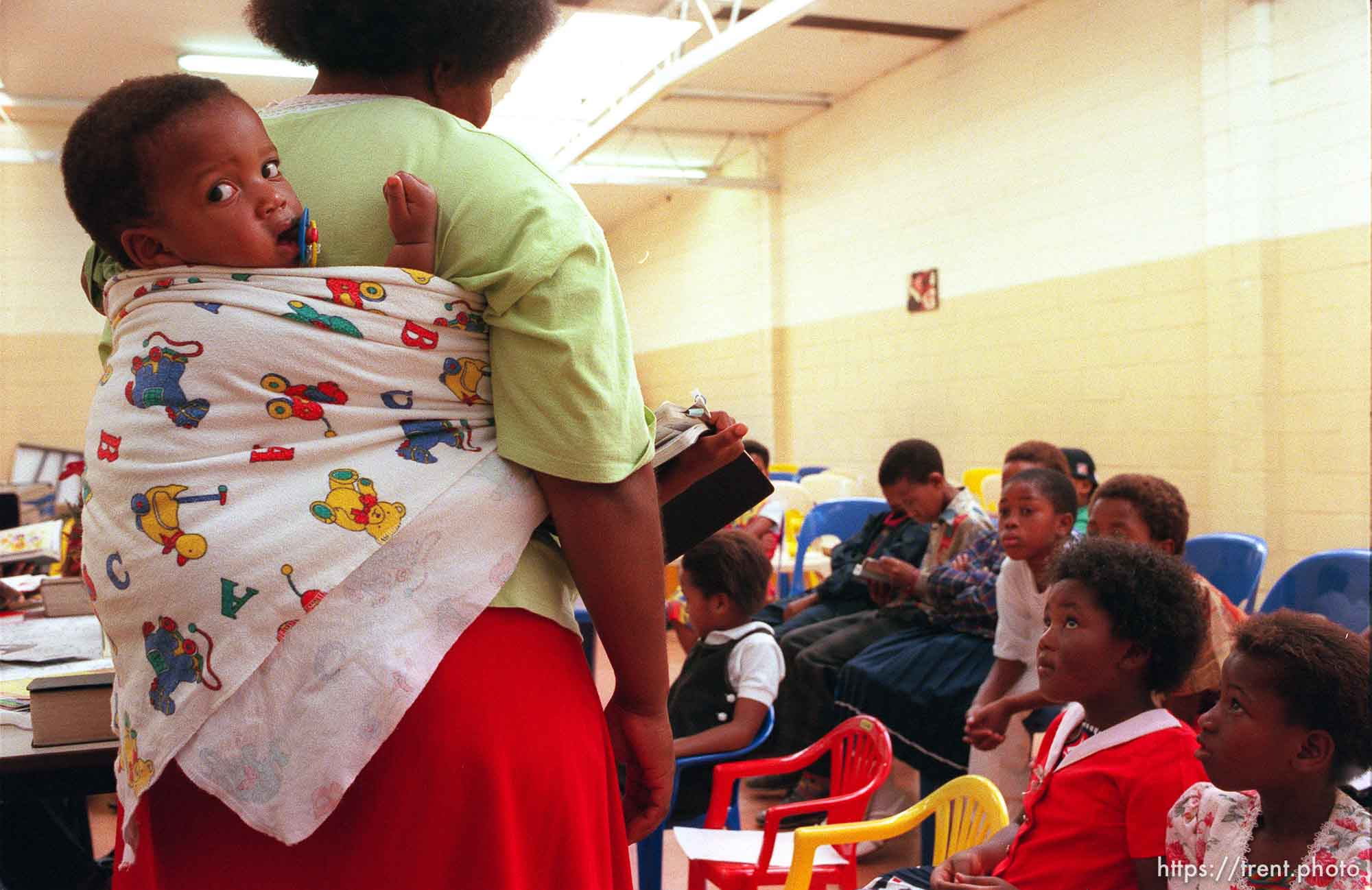 Zekey Tshetu (15 months old) on his mother, Thirsly's back at an LDS primary meeting.