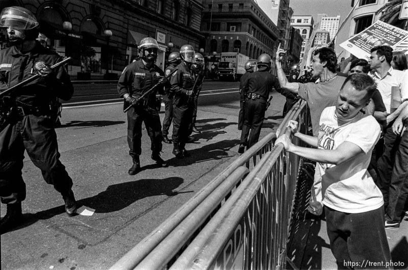 Guy flips off police whil people pull at barricades at Act-Up protest during visit of President Bush