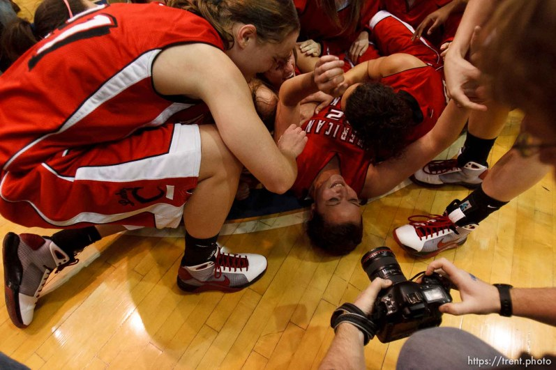 Taylorsville - American Fork players collapse in a dog pile at center court, celebrating their championship win over Riverton. Riverton vs. American Fork High School girls basketball, 5A State Championship game Saturday February 28, 2009 at Salt Lake Community College. craig dilger