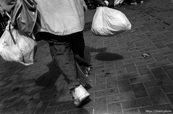 Man carrying bags. Leica hip shots on the street.