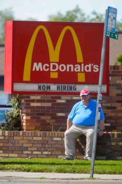 guy under McDonald's sign, now hiring, Wednesday June 22, 2016.