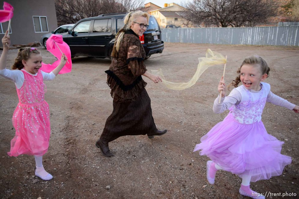 (Trent Nelson | The Salt Lake Tribune) A princess party was thrown for several young FLDS girls in Colorado City, Ariz., Friday March 16, 2018, as a reward for reading books. Lolly (purple) and Kathy (pink) Bistline run with Christine Marie Katas.