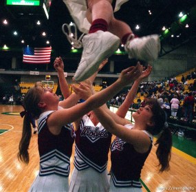 North Sevier cheerleaders (left to right) Ashley Burr, Jennifer Brown, and Ashlee McKinlay prepare to catch Laura Leaming (top) during a game in the state championship basketball tournament.
