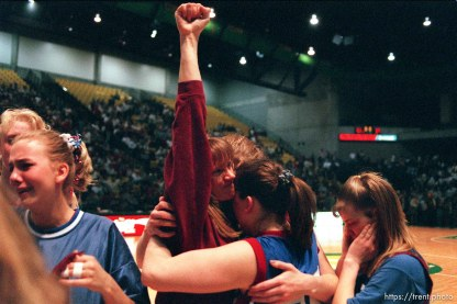 North Sevier girls' basketball coach Lexa Larsen raises her first to the Wolves' fans after losing in the state championship game to Beaver. Embracing the coach are Shadoe Shaheen (25) and Ann Braithwaite. At right is Chasity Peterson.