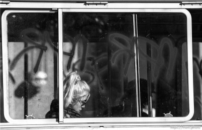 Woman on bus with graffiti on window.