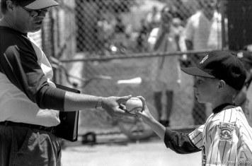 Coach gives player a game ball at Yankee baseball game