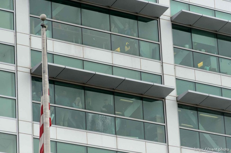 (Trent Nelson   The Salt Lake Tribune) People inside the Federal Building look down as protesters block off an intersection downtown after a rally against a visit by President Donald Trump, Monday December 4, 2017.