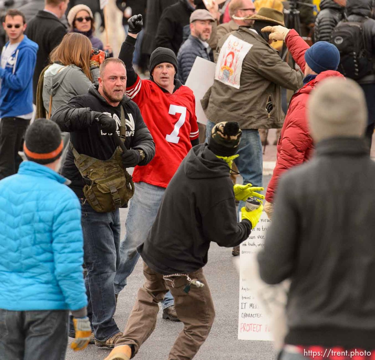 (Trent Nelson | The Salt Lake Tribune) A man pulls out a self defense baton as another man prepares to throw a drink at him. Protesters rally against a visit by President Donald Trump, Monday December 4, 2017.