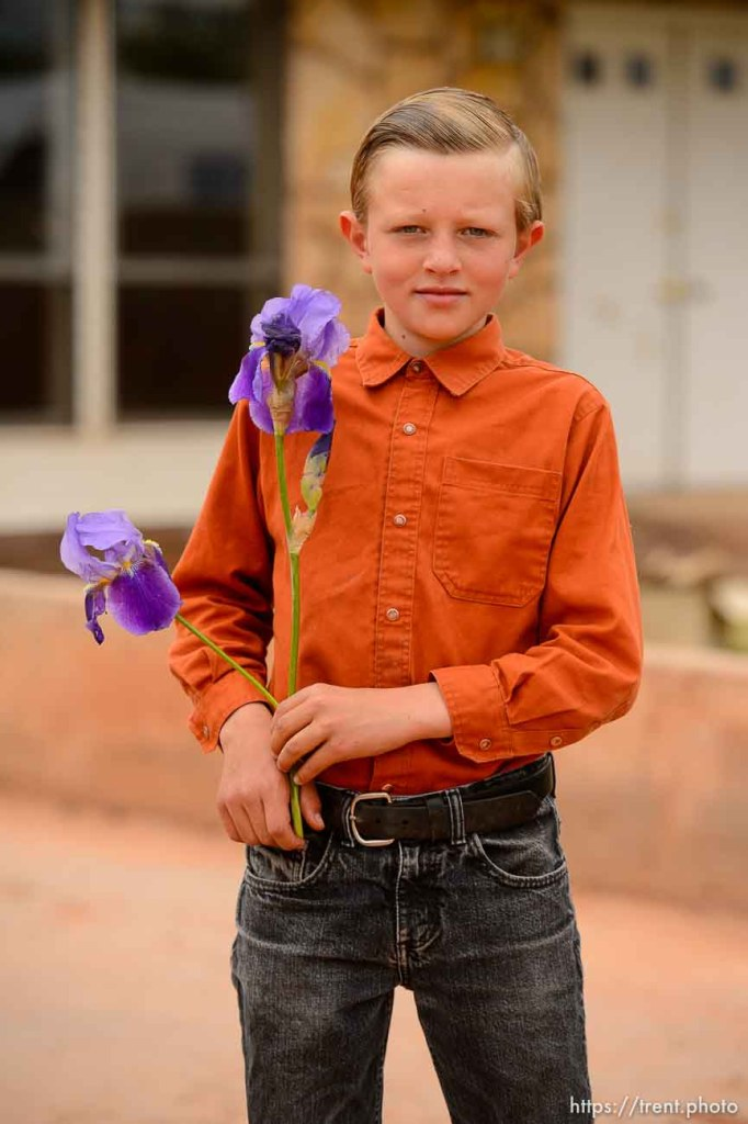 Trent Nelson | The Salt Lake Tribune An FLDS boy stands in front of the Colorado City, AZ, home he is being evicted from, holding flowers he would later leave on a UEP Trust employee's truck, Tuesday May 9, 2017.