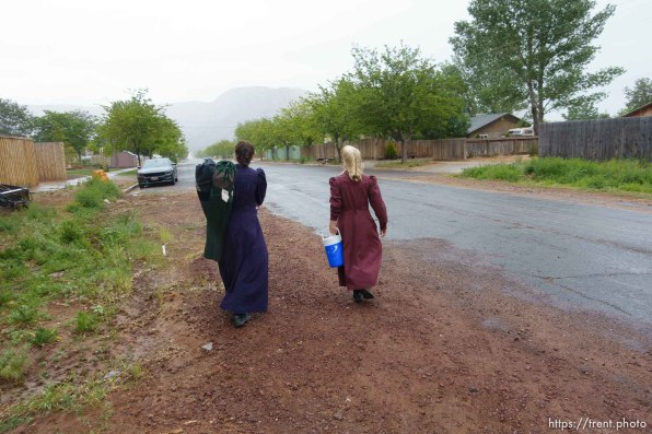 Trent Nelson | The Salt Lake Tribune Two FLDS women are evicted from a home in Colorado City, AZ, Tuesday May 9, 2017, and walk off in the rain.