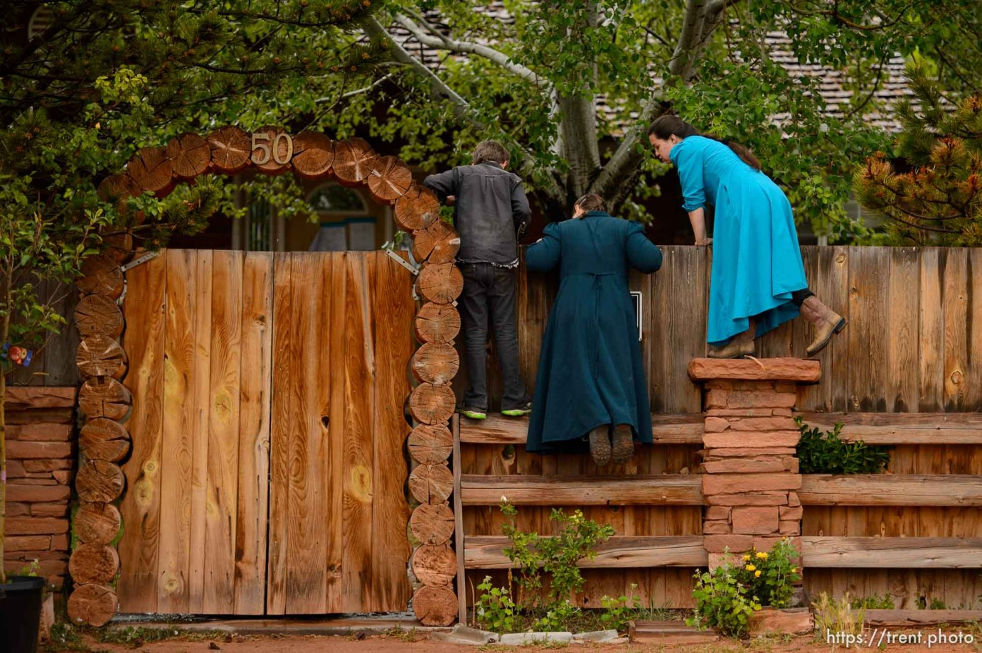 Trent Nelson   The Salt Lake Tribune FLDS children look over a wall as the UEP Trust has the locks changed on an FLDS home in Colorado City, AZ, Wednesday May 10, 2017.