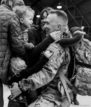 "(Trent Nelson | The Salt Lake Tribune) Staff Sergeant Sean Sullivan is welcomed home by his wife Kim and children Mae and Simon as almost 100 Soldiers from Utah Army National Guard's Echo Battery, 1st Battalion, 145th Field Artillery, ""Big Red"" return after a 10-month Middle East deployment, on Tuesday April 9, 2019 at Wright Air Base in Salt Lake City. Sullivan's mother Ilean at left."