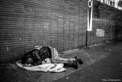 Homeless man sleeping on street.
