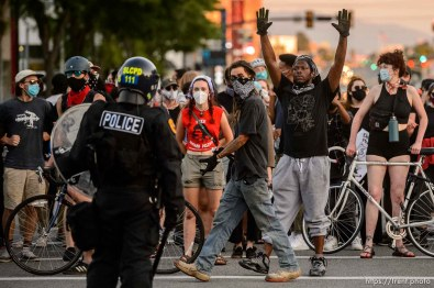 (Trent Nelson | The Salt Lake Tribune) Protesters face a line of police at 500 South State Street in Salt Lake City on Thursday, July 9, 2020.