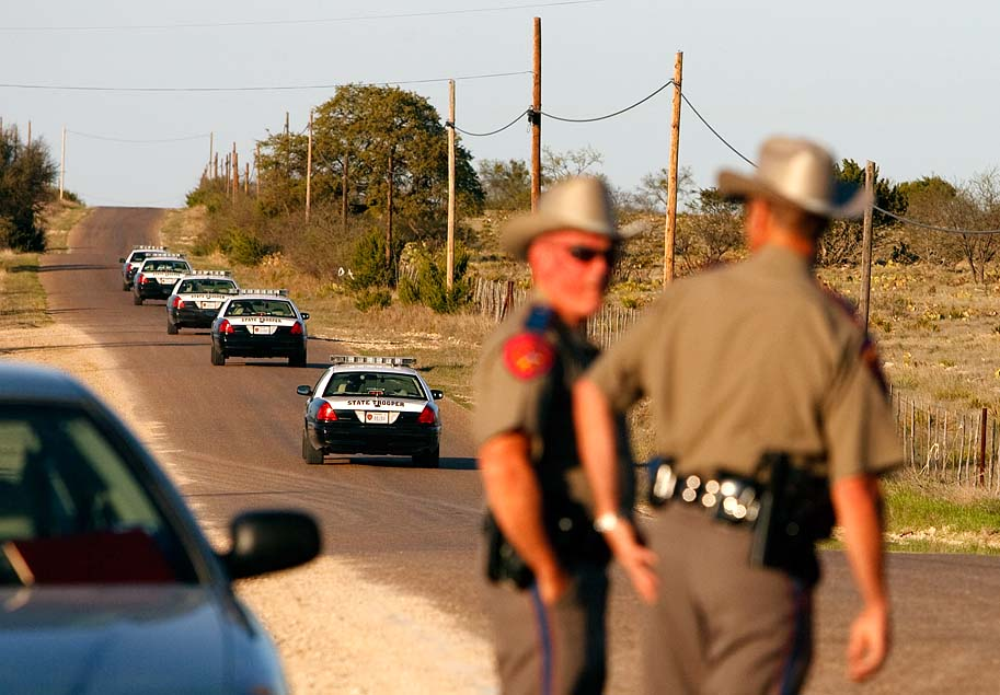 Eldorado, Texas - As law enforcement officials fearing a Waco-type incident prepare to breach the polygamous sect's temple at the YFZ Ranch, Texas State Troopers speed through a roadblock, en route to reinforce the assault which would meet with only minimal non-violent resistance.