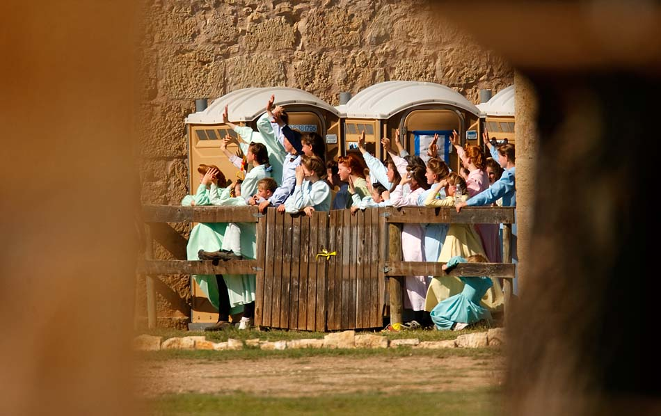 San Angelo, Texas - Young FLDS women gather behind a fence at Fort Concho, waving to other FLDS women in another building out of view. Texas Child Protective Services and Texas State Troopers made every effort to keep the nearly 500 women and children in custody out of view, going so far as to confiscate cel phones and other electronic devices.