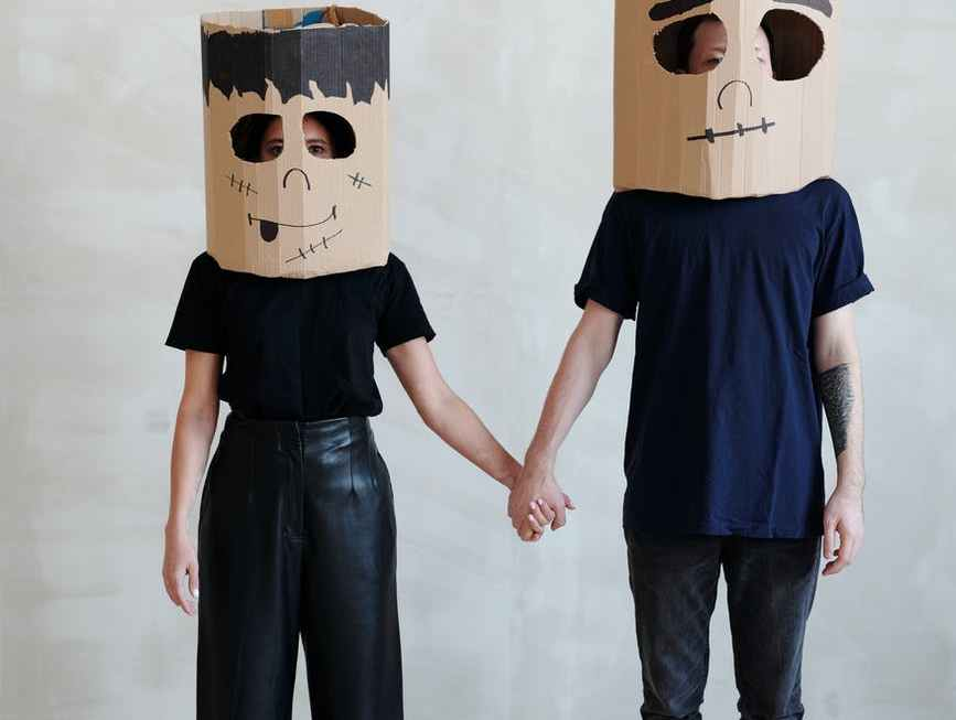 a couple wearing diy cardboard box mask while holding each other s hands