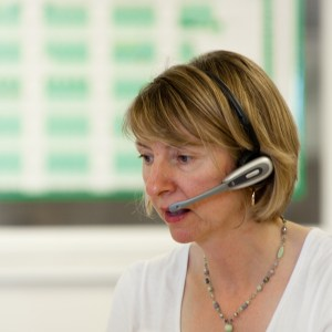Not a stock-shot of a woman on phone wearing headset with microphone
