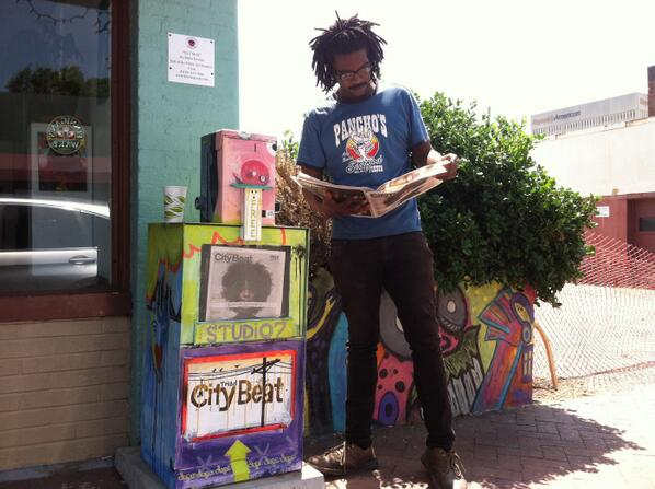 The artist Deezo reads a copy of Triad City Beat next to the box he painted on Trade Street.