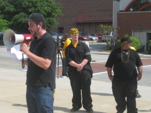 Eric speaking at a rally, with Bam and Jay behind him.