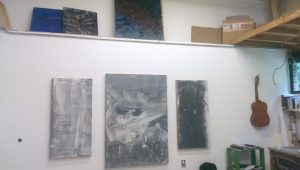 A lone guitar hangs next to three sprawling canvases prompting viewers to wonder if it is also art. (Sayaka Matsuoka)