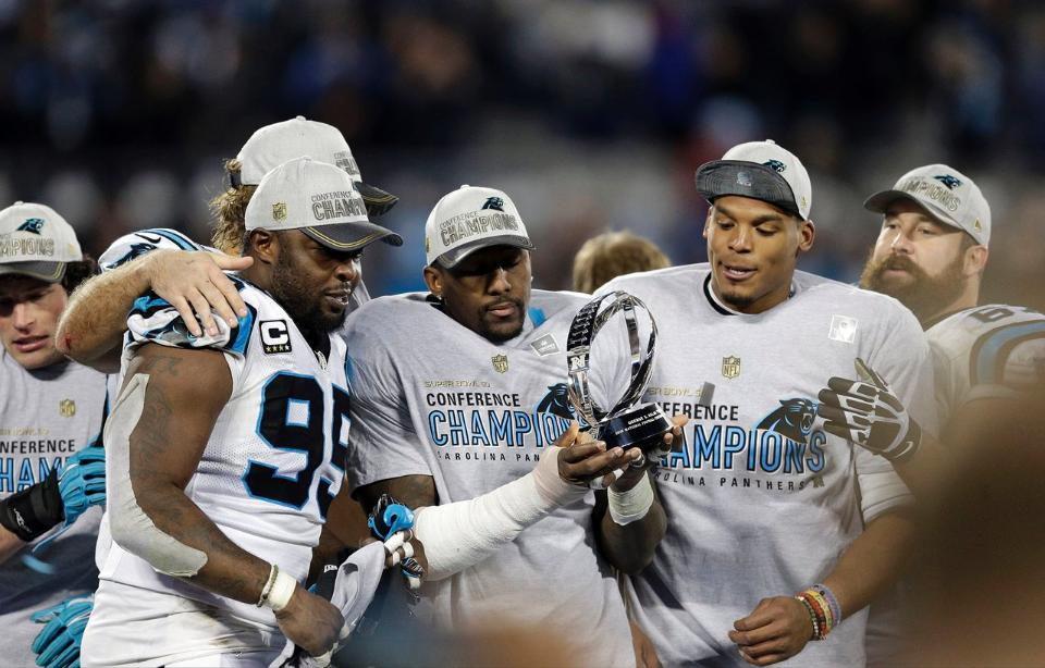 Kawann, TD and Cam share a moment with the George Halas Trophy. [courtesy Panthers.com]