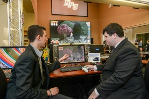 """Sam Schoenfeld (r) and Michael Messer discuss their brainchild, """"Guinevere and the Fallen King,"""" in the High Point University game lab. [courtesy photo]"""