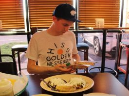sam-looks-at-the-menu-at-mi-casita-mexican-restaurant-with-food-in-front-of-him