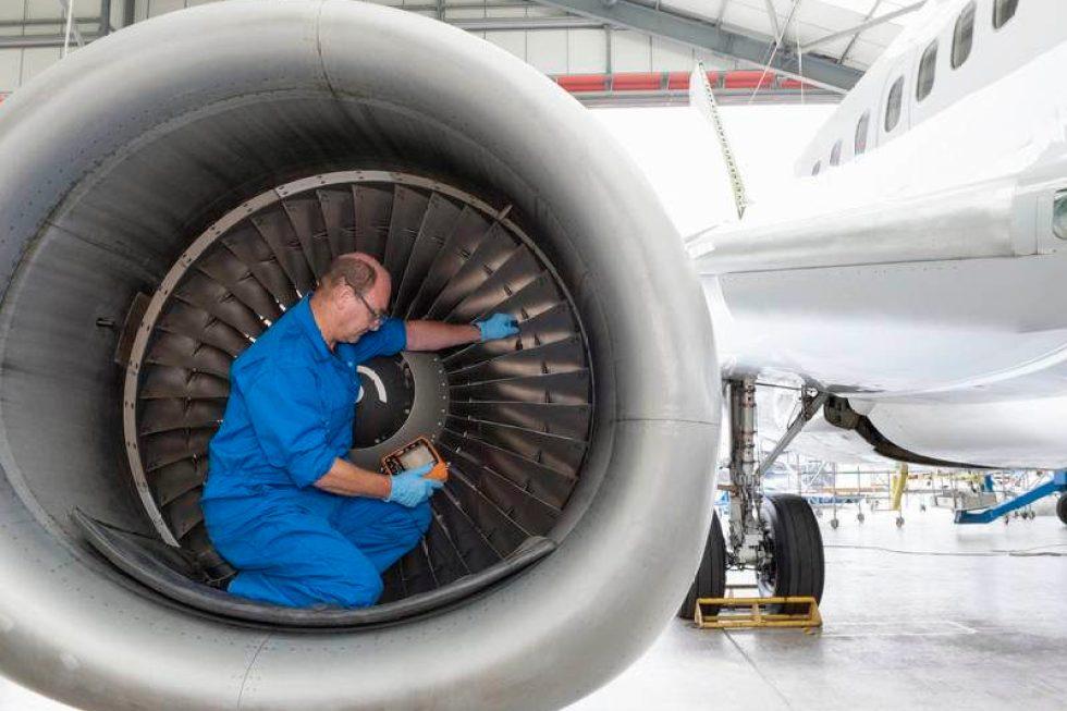 Engineer testing engine of passenger jet in hangar