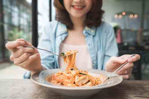 Beautiful happy Asian woman eating a plate of Italian seafood spaghetti at restaurant or cafe while smiling and looking at food.