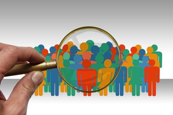 Imagen que muestra una lupa estudiando a un grupo de gente, mostrando así como la sociología nos estudia a todos como conjuntos sociales.