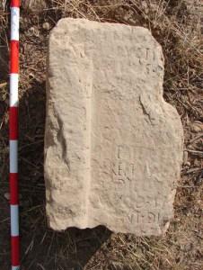Fragment de pedra amb restes epigràfiques, en el lloc de la troballa.