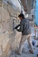 Restauració de la torre. El restaurador Albert Gaset posant al descobert una de les espitlleres de la torre.