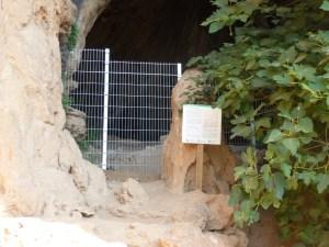 5. Vista de l'entrada de la cova des de fora, amb el plafó informatiu i la tanca