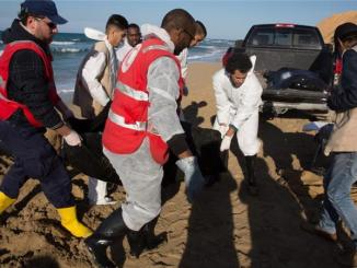 Libyan Red Crescent workers recovering bodies of drowned migrants from a beach east of the city of Tripoli, Libya. PHOTO: AL JAZEERA